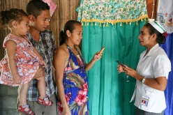 A midwife teaching an expectant mother and her family about the Liga Inan program in East Timor