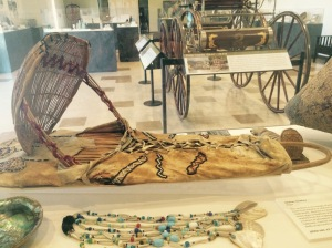 Two California Indian cradle boards and a Gold Rush era wagon on display at the Collections Resource Center in Sacramento